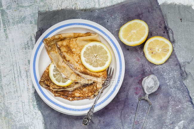 Top view of crepes with lemon slices on plate — Stock Photo