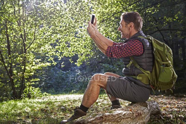 Escursionista seduto sul tronco d'albero e scattare selfie nella foresta — Foto stock