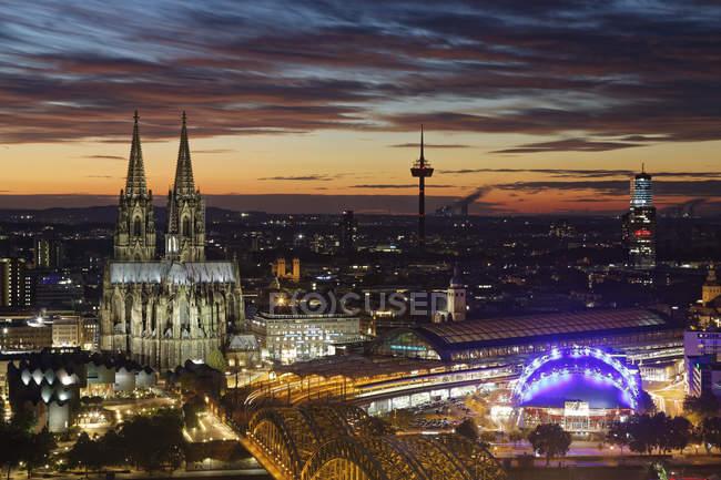 Alemania, Colonia, ve a la ciudad iluminada desde arriba en el crepúsculo vespertino - foto de stock