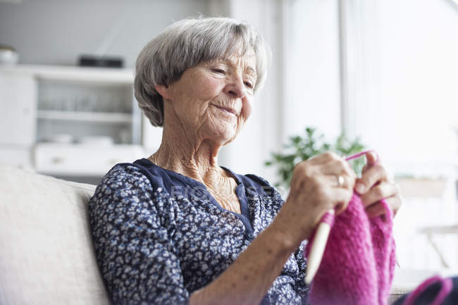 Portrait of knitting senior woman sitting on couch at home — Stock Photo