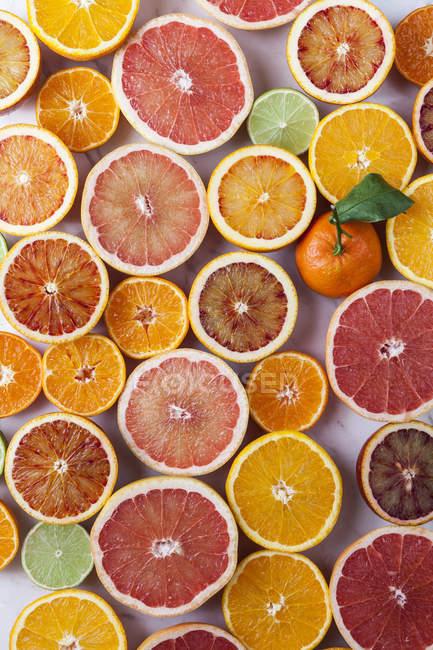 Moitiés de différents agrumes et une mandarine entier — Photo de stock