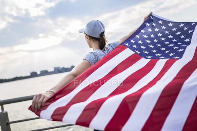 Задній вид жінка в Бейсболки тримає американський прапор — стокове фото