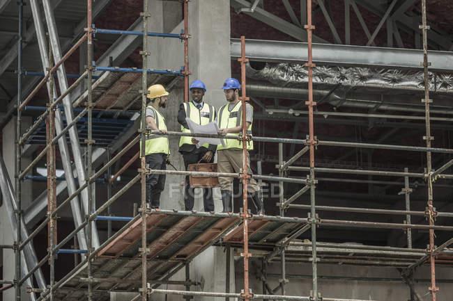 Bauarbeiter und Geschäftsmann diskutieren Bauplan auf Baugerüst — Stockfoto