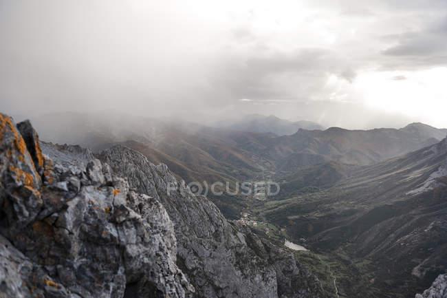 Spain, Picos de Europa, mountainscape under clouds over hill — Stock Photo
