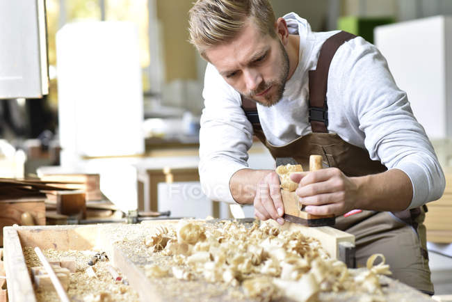 Carpenter working with plane in workshop — Stock Photo