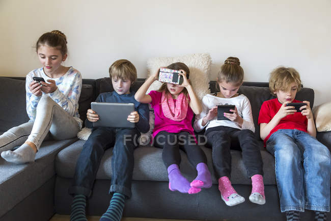 Изображение группы пяти детей, сидя на одном диване, с использованием различных цифровых устройств — стоковое фото