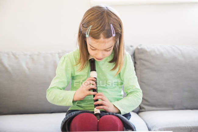 Little girl sitting on couch with recorder — Stock Photo