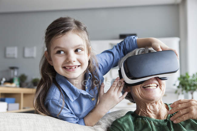 Senior woman and her granddaughter having fun with Virtual Reality Glasses at home — Stock Photo