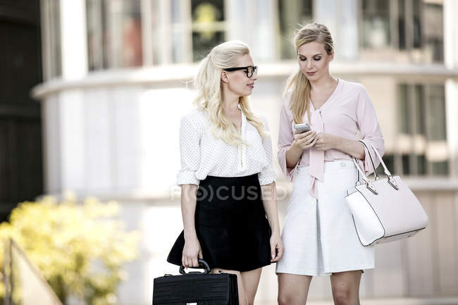 Two fashionable businesswomen with leather bags and smartphone — Stock Photo
