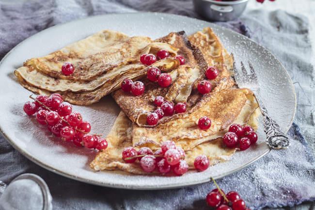 Crepes con ribes rosso cosparso di zucchero sulla piastra a velo — Foto stock