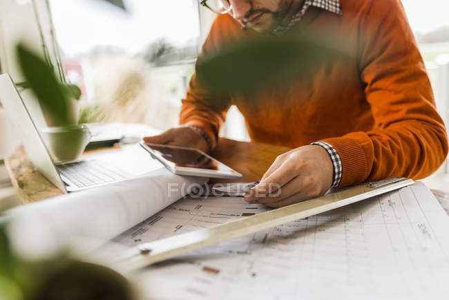 Man sitting with tablet and plan at desk — Stock Photo