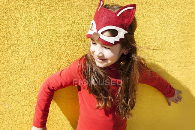 Ritratto di bambina con maschera animale davanti alla parete gialla — Foto stock