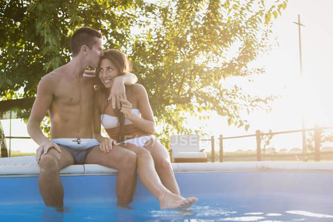 Junges Paar, entspannend und küssen am Beckenrand — Stockfoto