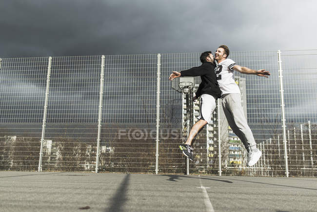 Two young basketball players jumping on each other — Stock Photo