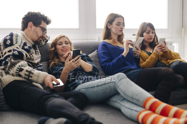 Four friends with smartphones on couch in living room hanging out — Stock Photo