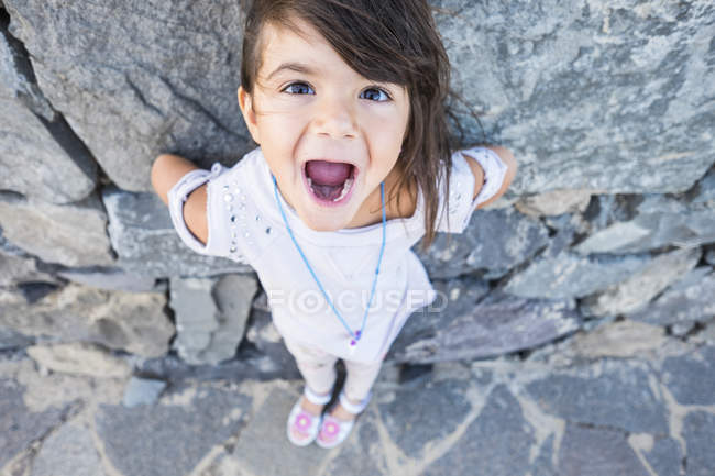 Portrait of little girl with mouth open in front of a rock face — Stock Photo