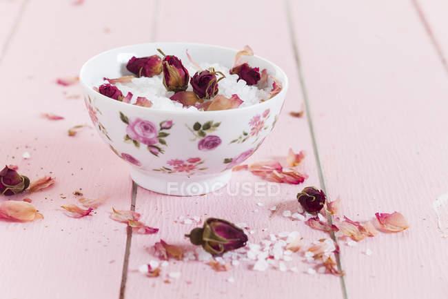Крупный план морской соли с сушеными цветами роз в чаше — стоковое фото