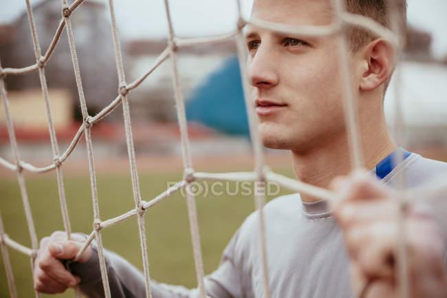 Молодой человек в футбольных воротах — стоковое фото