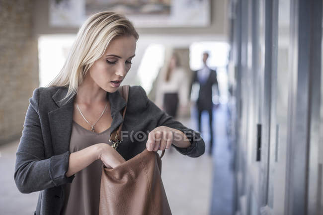 Young businesswoman looking down in handbag — Stock Photo