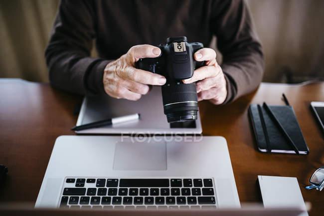 Fotógrafo senior, trabajando con su ordenador en casa . - foto de stock