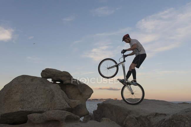 Велосипедист прыгает на скале на пляже Льорет-де-Мар на закате — стоковое фото