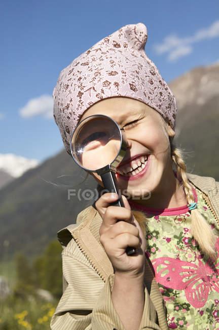 Счастливая девушка смотрит через увеличительное стекло — стоковое фото