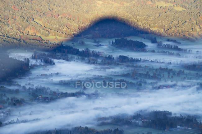 Allemagne, Haute Bavière, brouillard le matin dans la vallée de l'Isar, ombre de la montagne, vue Geierstein — Photo de stock