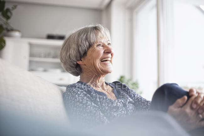 Portrait of laughing senior woman sitting on couch at home — Stock Photo