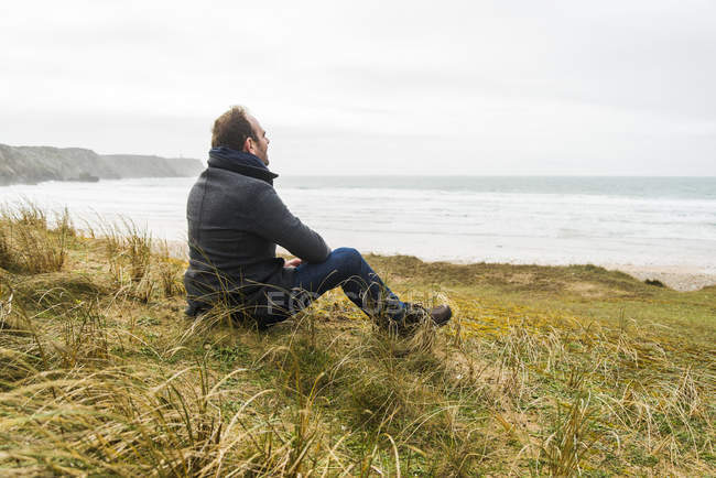 Thoughtful man sitting at the coast with cloudy sky — Stock Photo