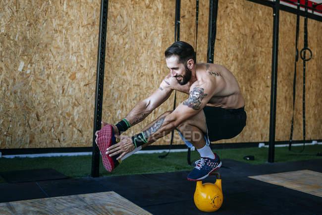 Mann, die Erhaltung des Gleichgewichts auf eine Kettlebell in Turnhalle — Stockfoto