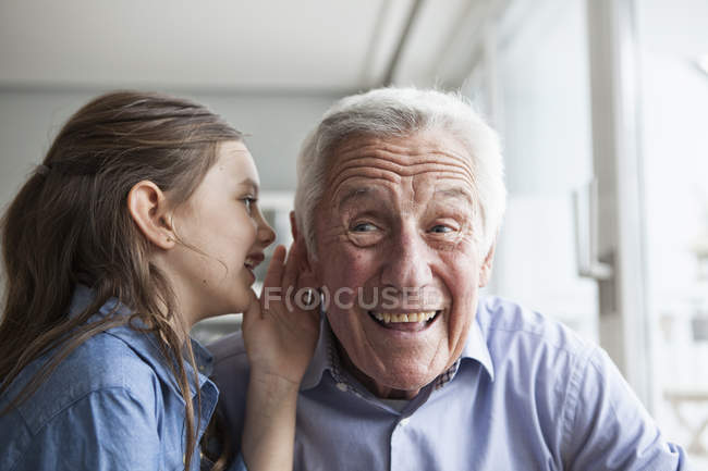 Granddaughter wispering something in the ear of her grandfather — Stock Photo