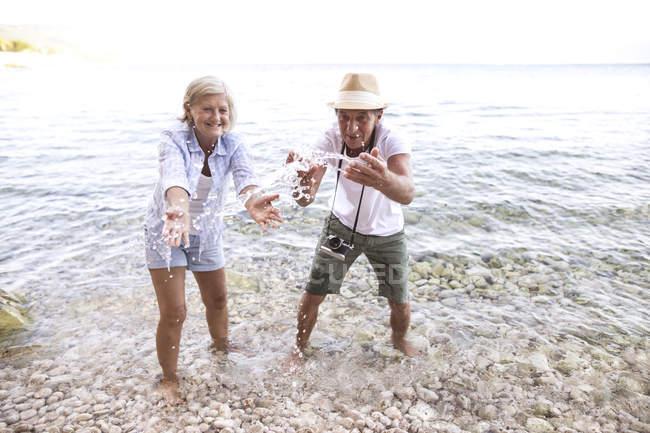 Активних старшим милий пара туристів бризки води на пляжі — стокове фото
