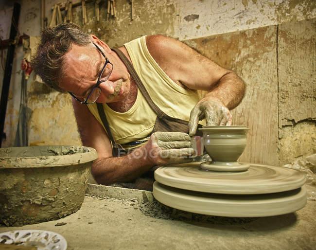 Поттер в мастерской работает над вазой — стоковое фото