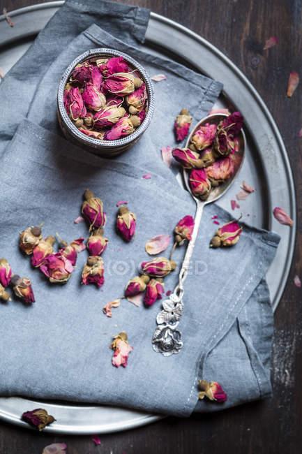 Tigela de flores de rosa secas e uma colher de prata em pano e bandeja — Fotografia de Stock