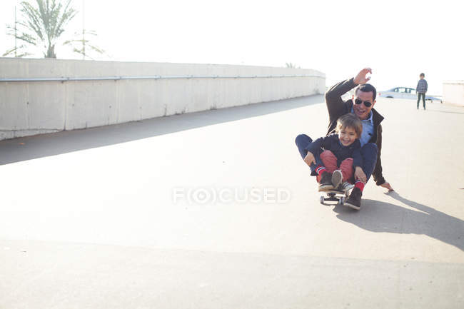 Uncle and kids doing skateboarding outdoors — Stock Photo