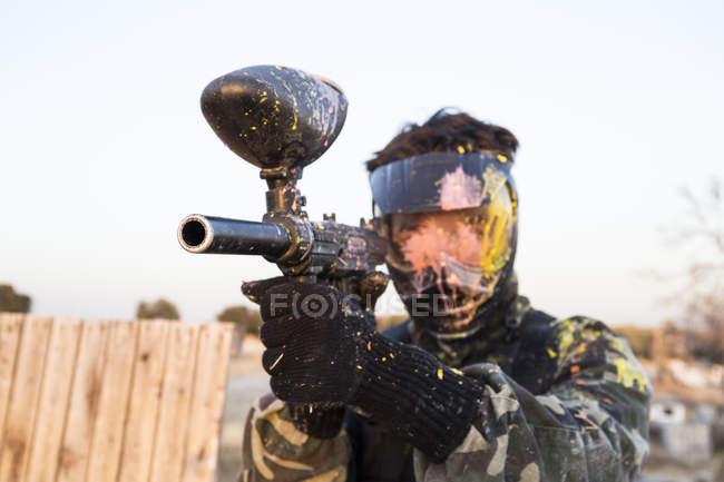 Пейнтболист в маске и пейнтбольном ружье с краской — стоковое фото