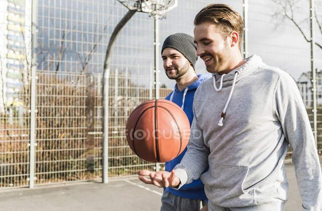 Два молодых баскетболиста с мячом на открытом воздухе — стоковое фото
