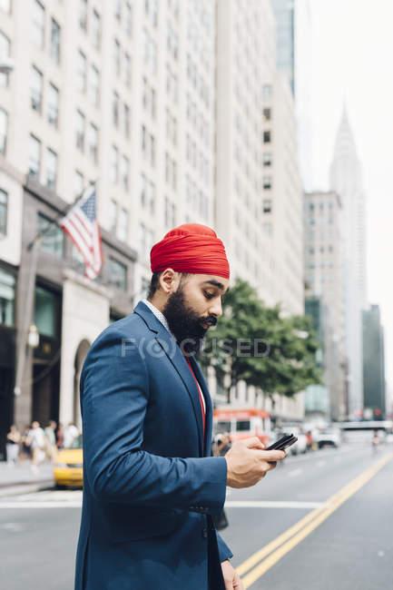 Индийский бизнесмен ходит по городской улице с телефоном, Манхэттен, Нью-Йорк, США — стоковое фото