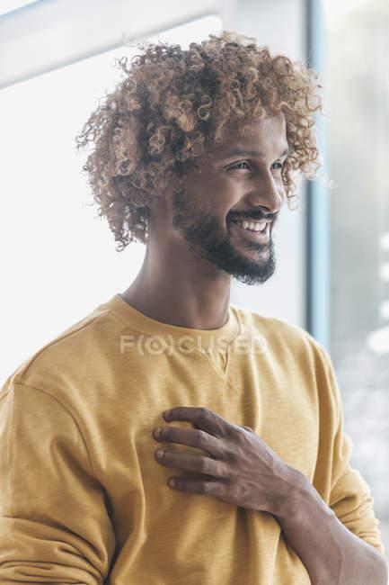 Усміхаючись молода людина з афро кучері дивлячись away, портрет — стокове фото