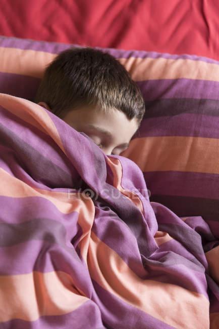 Junge schläft im Bett unter gestreifter Decke — Stockfoto