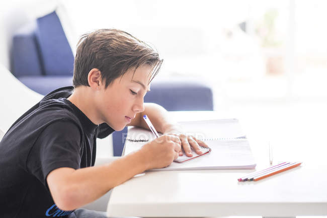 Boy doing homework, side view — Stock Photo