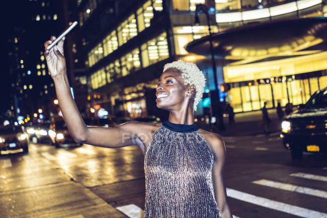 Щасливі жінка бере selfie на Таймс-сквер в нічний час, Нью-Йорк, США — стокове фото