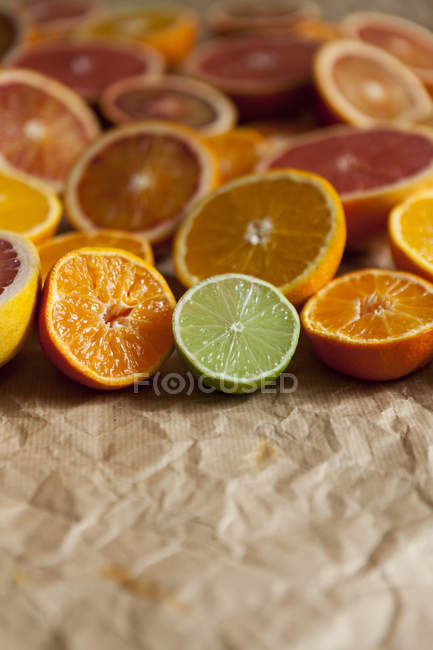 Halves of different citrus fruits on crumpled brown paper — Stock Photo