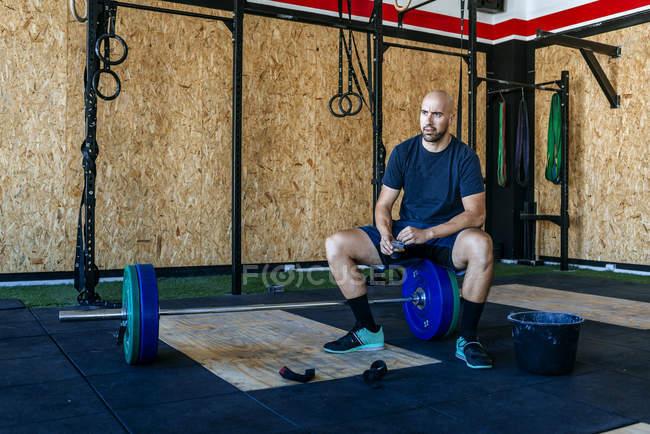 Kaukasische sportlichen Mann ruht auf Langhantel im Fitness-Studio — Stockfoto