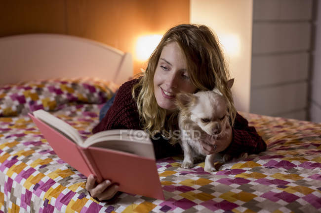 Smiling woman lying on bed with her dog reading a book — Stock Photo