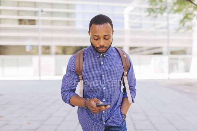 Африканец с рюкзаком смотрит на свой телефон на городской улице — стоковое фото