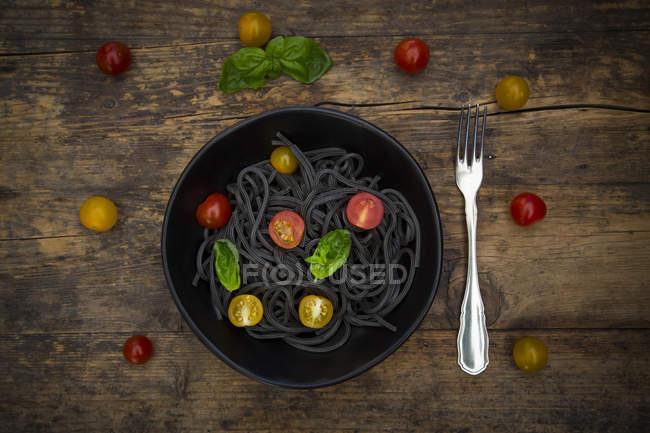 Schüssel Spaghetti al nero di seppia mit Tomaten und Basilikumblättern auf dunklem Holz — Stockfoto