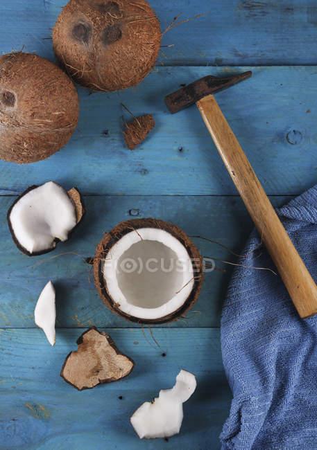 Apertura de coco con martillo sobre madera azul - foto de stock