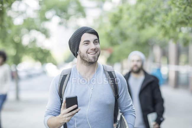 Jovem caminhando na cidade com telefone ouvindo música — Fotografia de Stock