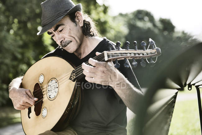 Syrian refugee playing Arabian lute oud — Stock Photo